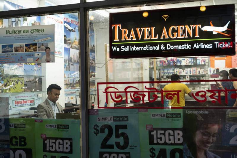 """Zakaria Masud, left, works in his Queens travel agency after it reopened during the coronavirus pandemic, June 18, 2020, in New York's Jackson Heights neighborhood. """"I think we're losing 50 percent of the revenue. But I think we can survive,"""" said Masud. (AP Photo/Mark Lennihan)"""