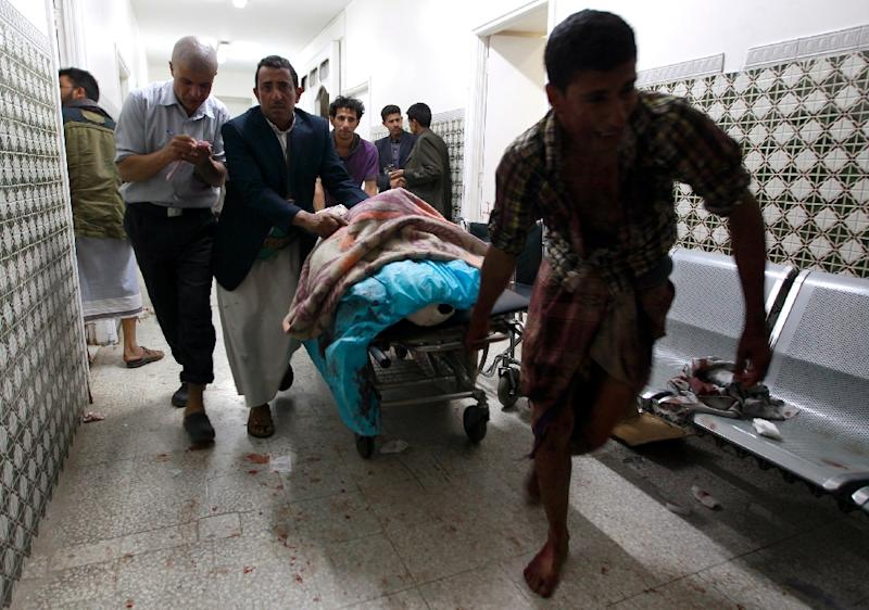 Yemenis transport a severely injured man on a gurney as he arrives at a hospital in Sanaa after being injured when two suicide bombers hit a Shiite mosque in quick succession, September 2, 2015