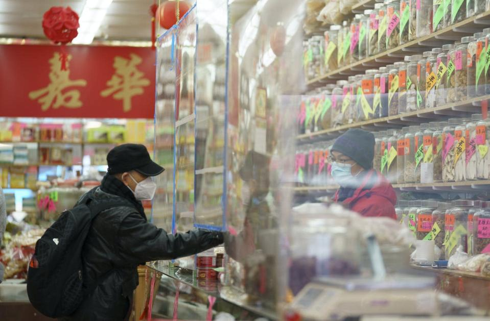 A man wearing a mask shops at a store in Chinatown in Vancouver. The cashier is behind a plastic sheet.