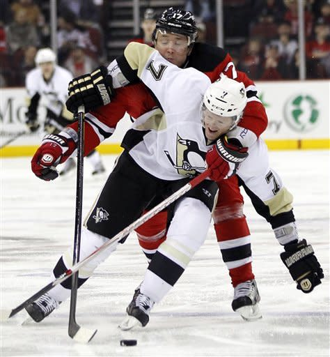 Pittsburgh Penguins' Paul Martin (7) and New Jersey Devils' Ilya Kovalchuk, of Russia, get entangled during the second period of an NHL hockey game on Sunday, Feb. 5, 2012, in Newark, N.J. (AP Photo/Julio Cortez)