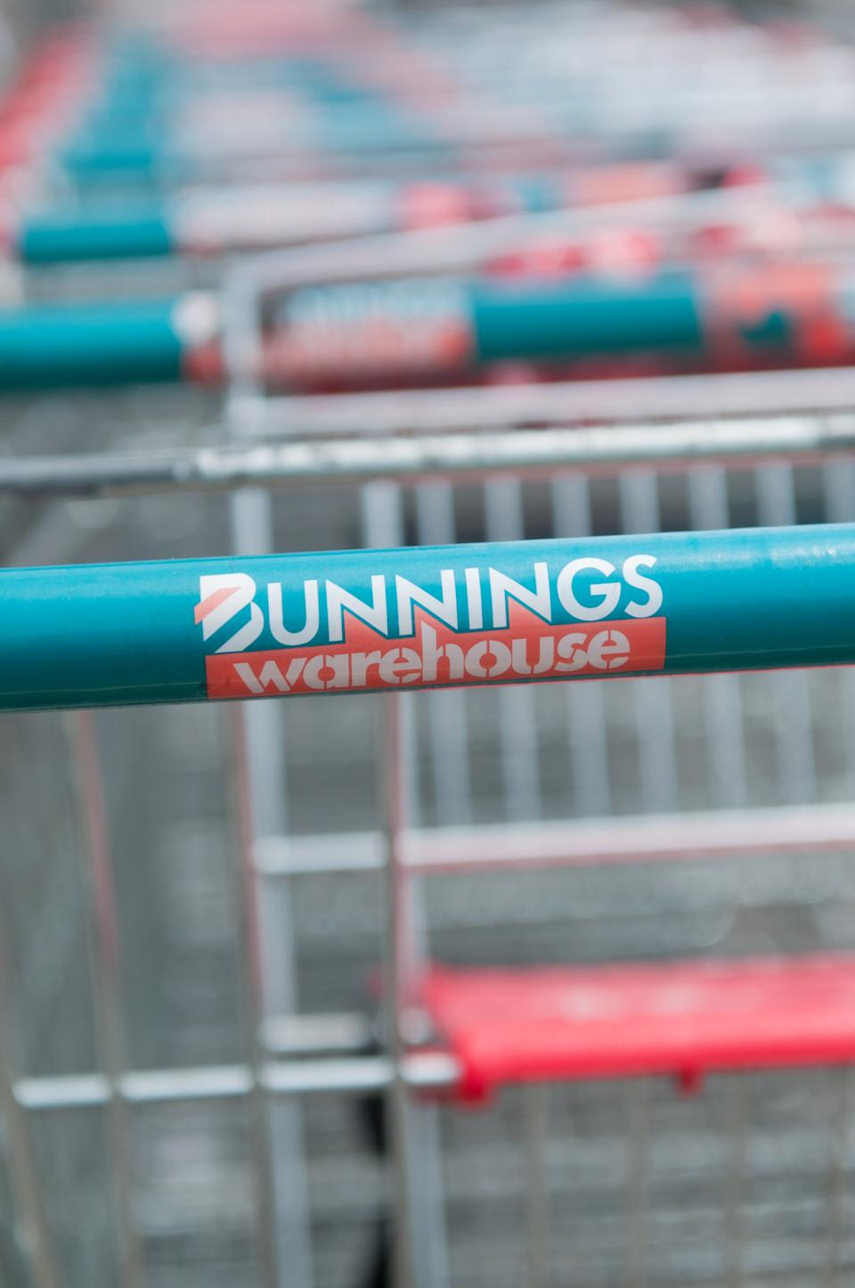 Close up of the Bunnings Warehouse logo on a trolley hand located in a trolley bay. Bunnings is a very popular hardware/diy store supplying both trade and diy enthusiasts, currently having the biggest market share of this industry within australia.