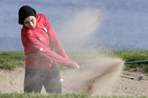 In this April 10, 2019 photo, Noor Ahmed, a member of the Nebraska NCAA college golf team, hits out of a sand trap during practice in Lincoln, Neb. Ahmed is the only golfer at the college level or higher known to wear a hijab while competing. She hopes Muslim girls are watching her and encouraged to chase their dreams in environments where they might encounter fear, uncertainty and hostility. (AP Photo/Nati Harnik)