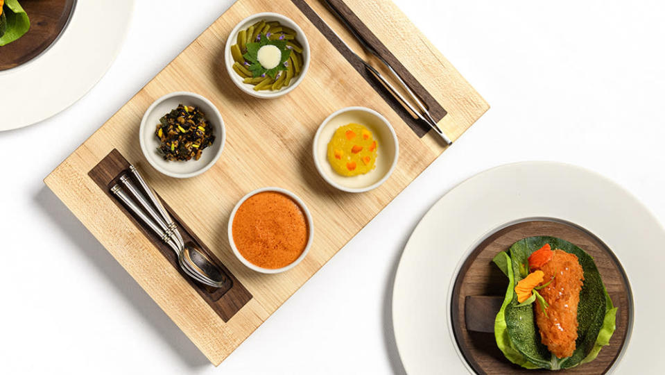 A selection of vegetable-based dishes, including fried peppers with Swiss chard, at Daniel Humm's reimagined Eleven Madison Park. - Credit: Evan Sung