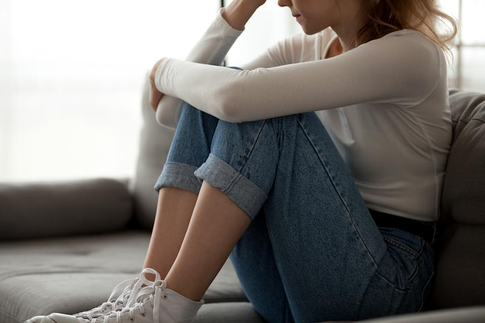 Close up sorrowful woman sitting on couch alone at home. Frustrated confused female feels unhappy, having a problem in personal life, quarrel or break up with boyfriend, unexpected pregnancy concept