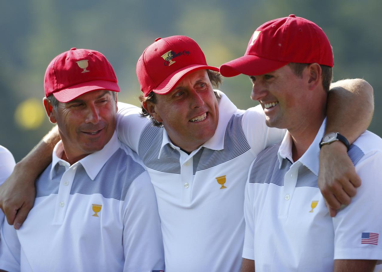 U.S. golfer Phil Mickelson puts his arms around team captain Fred Couples (L) and player Webb Simpson (R) during a team photo session prior to their first practice round for the 2013 Presidents Cup golf tournament at Muirfield Village Golf Club in Dublin, Ohio October 1, 2013. REUTERS/Chris Keane (UNITED STATES - Tags: SPORT GOLF)