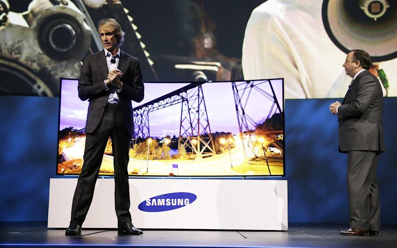 Director Michael Bay, left, and Samsung Electronics America Executive Vice President Joe Stinziano introduce a 105-inch ultra high definition curved television during a news conference at the International Consumer Electronics Show, Monday, Jan. 6, 2014, in Las Vegas. (AP Photo/Isaac Brekken)