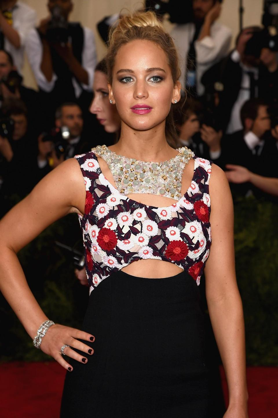 <p>At the Met Gala in 2015, Jennifer paired a high bun with her elaborate dress. Pink lipstick and a bronzed complexion completed the look. [Photo: Getty] </p>