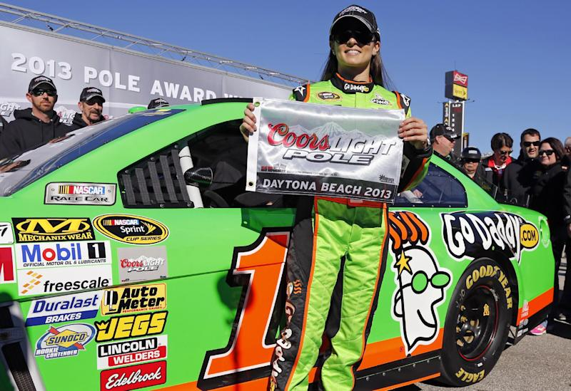 Danica Patrick displays the flag after winning the pole during qualifying for the NASCAR Daytona 500 Sprint Cup Series auto race at Daytona International Speedway, Sunday, Feb. 17, 2013, in Daytona Beach, Fla. Patrick became the first woman to secure the top spot for any Sprint Cup race. (AP Photo/Terry Renna)