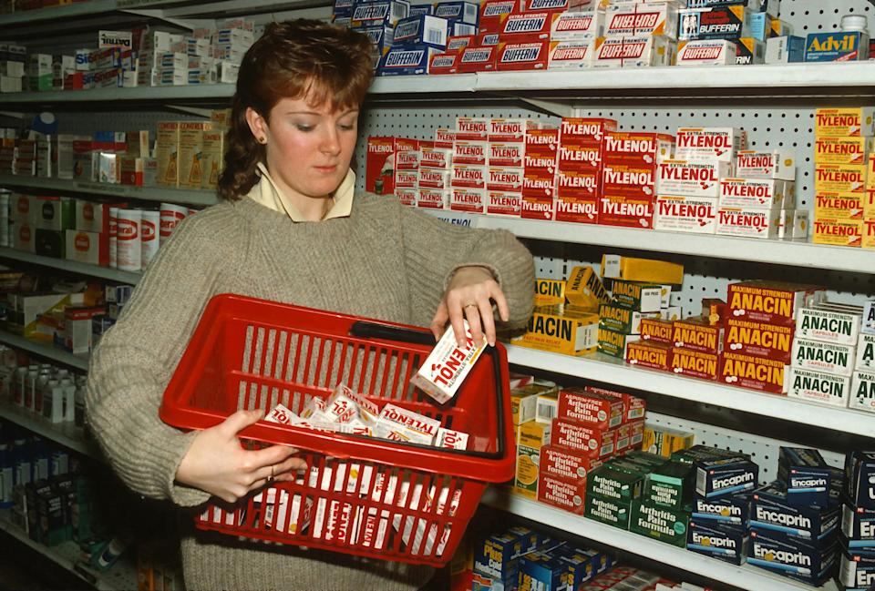 Drugstore clerk removes Tylenol capsules from the shelves of a pharmacy. Source: Getty Images