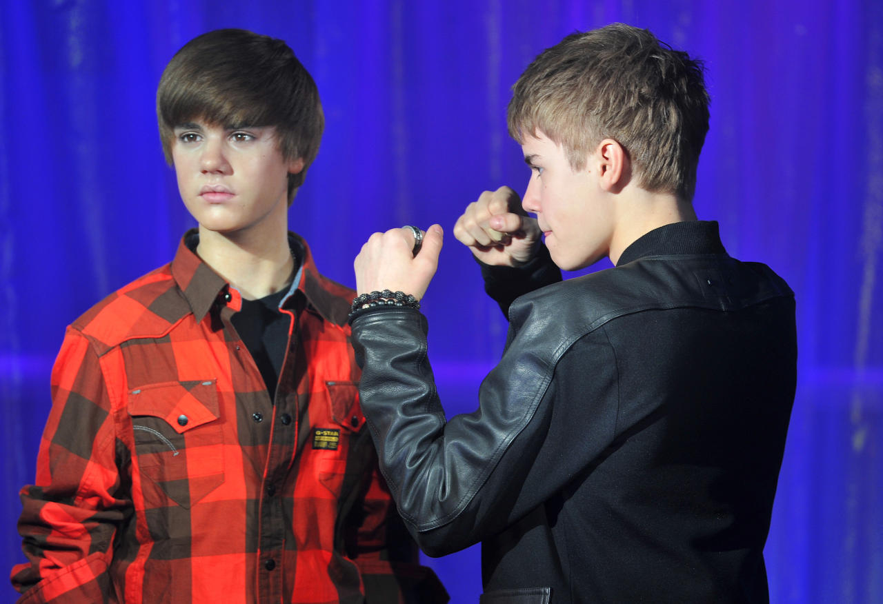 Canadian singer Justin Bieber (black top) poses with a waxwork model of himself during an official unveiling at Madame Tussauds Wax Museum in central London March 15, 2011. REUTERS/Toby Melville