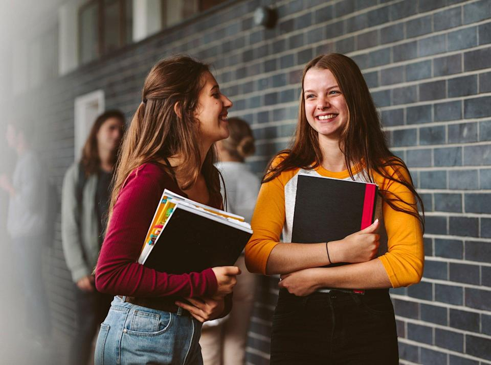 An image of two high school students in a hallway.