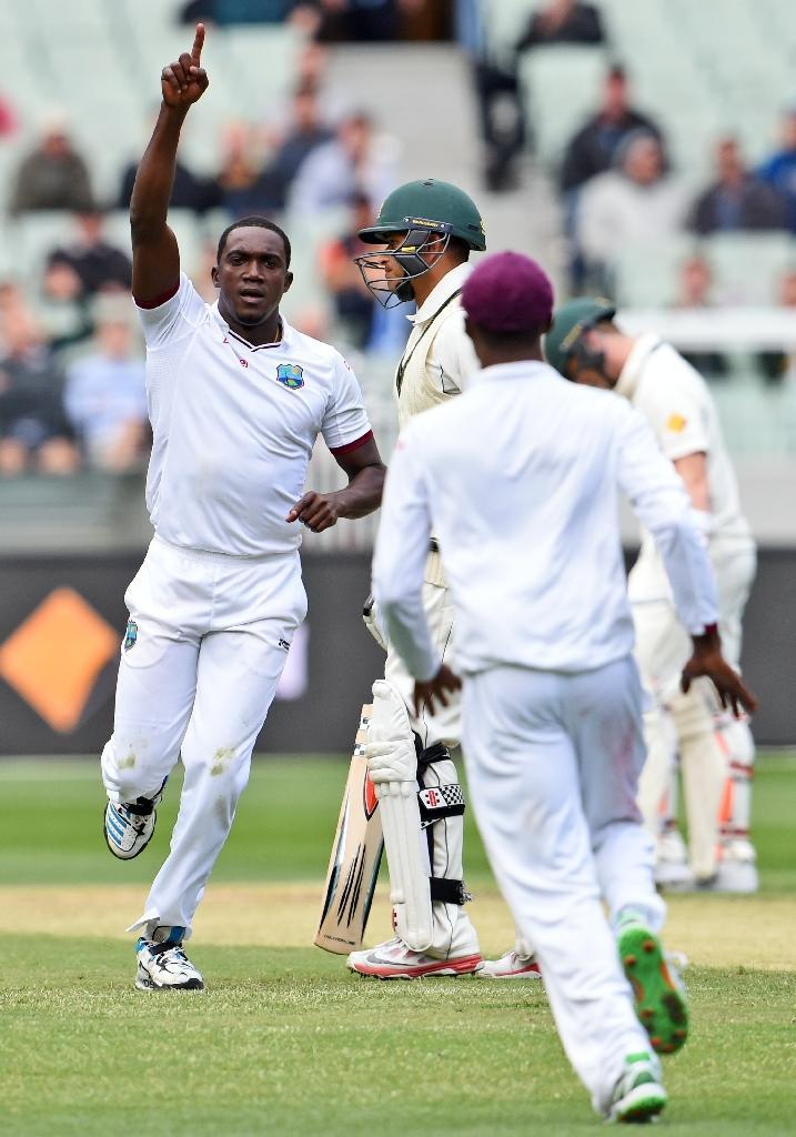 West Indies bowler Jerome Taylor (left) celebrates the dismissal of Australian century-maker Usman Khawaja (centre) on the first day of the second Test in Melbourne on December 26, 2015 (AFP Photo/William West)