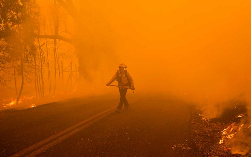 A firefighter emerges from a thick cloud of smoke while battling the Kincade Fire along Chalk Hill Road in Healdsburg, California on October 27, 2019. | PHILIP PACHECO/Getty Images