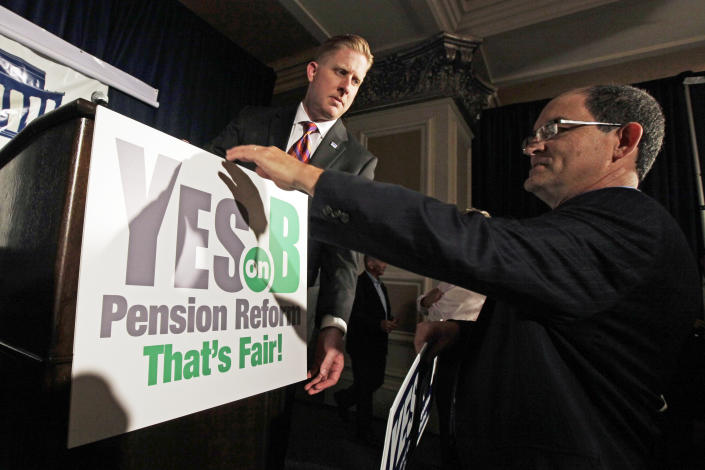FILE - Supporters of Proposition B, which would roll back public pensions, adjust a sign before a rally on election day in San Diego in this Tuesday, June 5, 2012 file photo. For years, companies have been chipping away at workers' pensions. Now, two California cities may help pave the way for governments to follow suit. Voters in San Diego and San Jose, the nation's eighth- and 10th-largest cities, overwhelmingly approved ballot measures last week to roll back municipal retirement benefits — and not just for future hires but for current employees. (AP Photo/Gregory Bull, File)