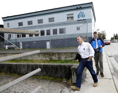 In this Oct. 10, 2014 photo, Republican Dan Sullivan, left, walks near the Petersburg Elks Lodge Hall after stopping at a luncheon where Alaska Gov. Sean Parnell was speaking in Petersburg, Alaska. The Republican, and former state attorney general, is challenging U.S. Sen. Dan Begich for his seat in the hotly contested race that some analysts say could tip the party balance of the U.S. Senate. At right, spokesman Mike Anderson checks the candidate's schedule and list of commitments for the rest of the day. (AP Photo/Ted S. Warren)