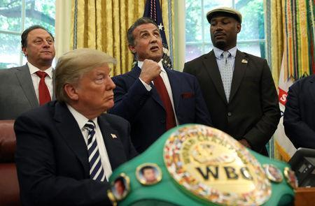 Boxer Lennox Lewis (R) stands by as actor Sylvester Stallone looks toward the heavens and offers up a punch in honor of the late Jack Johnson, the first black heavyweight boxing champion, whom U.S. President Donald Trump pardoned at the White House in Washington, U.S., May 24, 2018. REUTERS/Kevin Lamarque
