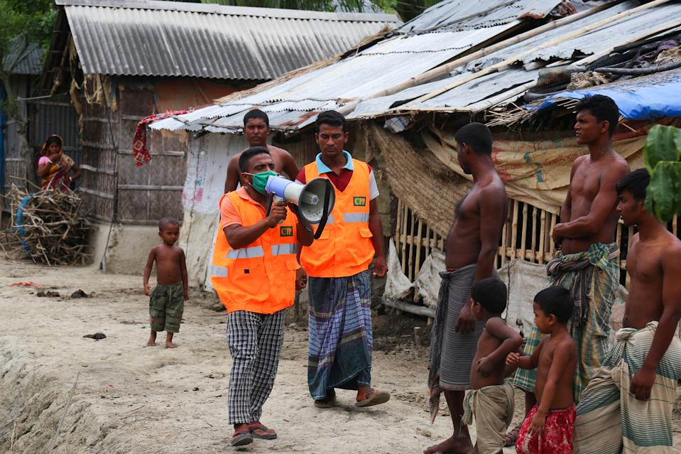 A Cyclone Preparedness Programme (CPP) volunteer uses a megaphone to urge residents to evacuate to shelters ahead of the expected landfall of cyclone Amphan in Khulna on May 19, 2020. (Photo by KAZI SHANTO/AFP via Getty Images)