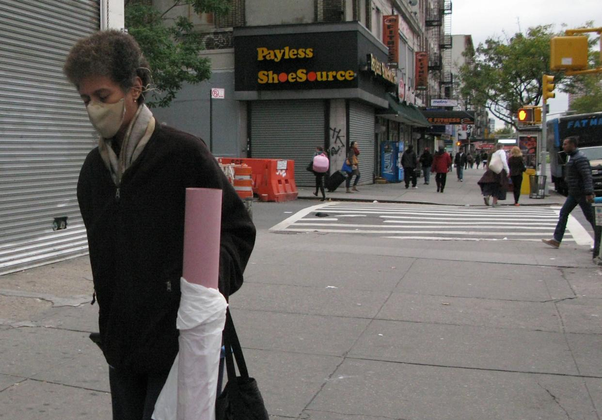A pedestrian, wearing a mask, walks near the apartment building of Dr. Craig Spencer on October 24, 2014 in New York.