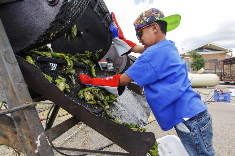 FILE - In this Aug. 9, 2017, file photo, Chris Duran Jr, 7 helps roast green chile with his family outside the Big Lots in Santa Fe, N.M. A hybrid version of a New Mexico chile plant has been selected to be grown in space as part of a NASA experiment, officials recently announced. (Gabriela Campos/Santa Fe New Mexican via AP, File)
