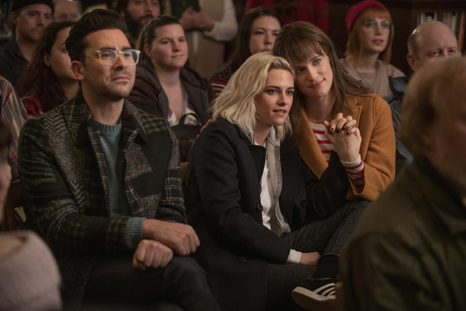 "This image released by Hulu shows Dan Levy, from left, Kristen Stewart, and Mackenzie Davis in a scene from ""Happiest Season."" (Lacey Terrell/Hulu via AP)"