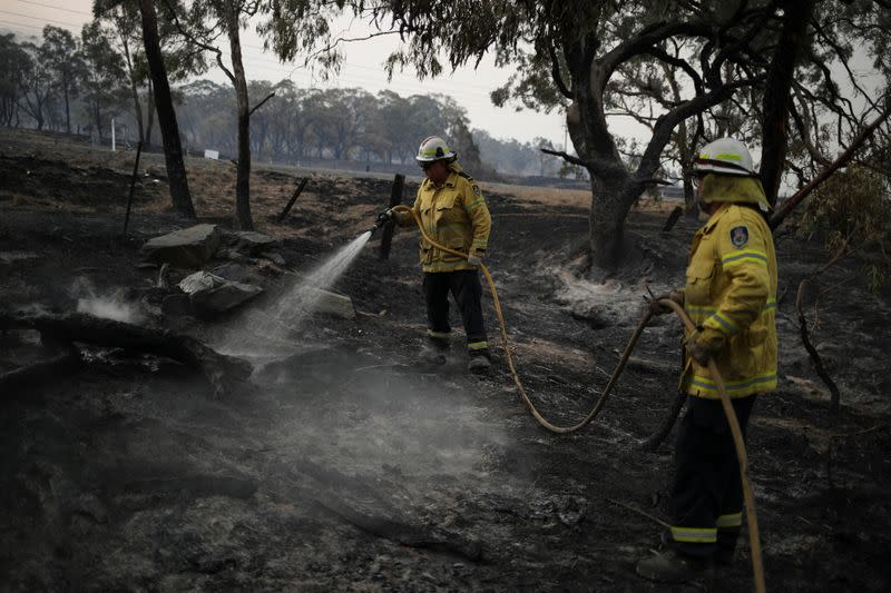 Firefighters spray water on smouldering patches left in the wake of a bushfire near Bumbalong