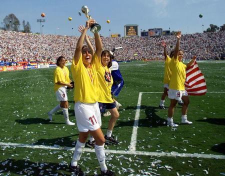 FILE PHOTO: Julie Foudy of the USA (C) holds up the Women's World Cup trophy after the USA beat China in the World Cup final on penalty kicks. At left is Mia Hamm (9) and at right is Shannon MacMillan, with flag/File Photo