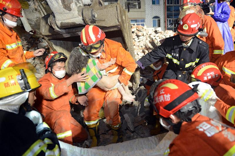 Rescuers carry three-year-old Wu Ningxil from the rubble more than 12 hours after the building she was in collapsed in Wenzhou, eastern China (AFP Photo/)
