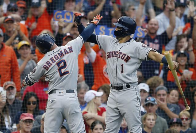 Houston Astros' Alex Bregman (2) celebrates his solo home run with Carlos Correa (1) during the third inning against the Boston Red Sox. (AP Photo)