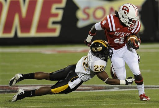 Western Kentucky wide receiver Rico Brown (4) runs through the tackle of Southern Mississippi defensive back Deron Wilson (22)in the first half of an NCAA college football game in Bowling Green, Ky., Saturday, Sept. 22, 2012. (AP Photo/Daily News, Joe Imel)