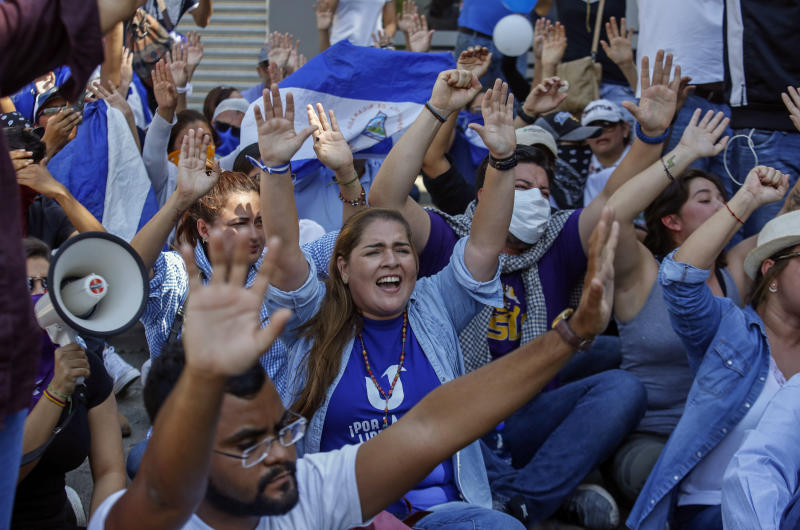Anti-government protesters yell slogans against President Daniel Ortega as they sit in the street where they are blocked by police from marching in Managua, Nicaragua, Wednesday, April 17, 2019. Police prevented the march to commemorate a year since Nicaraguan protesters took to the streets to oppose the government of President Daniel Ortega. (AP Photo/Alfredo Zuniga)