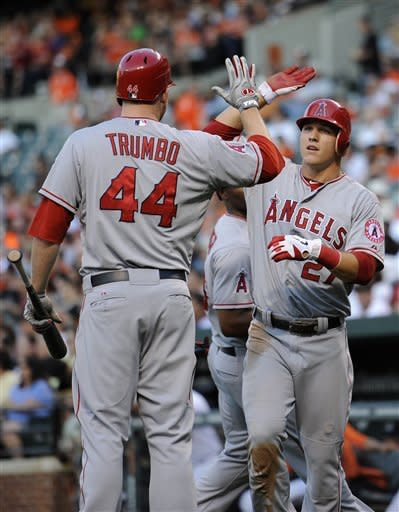 Los Angeles Angels' Mike Trout (27) celebrates with Mark Trumbo (44) after he scored on a single by Kendrys Morales during the third inning of a baseball game against the Baltimore Orioles, Wednesday, June 27, 2012, in Baltimore. (AP Photo/Nick Wass)