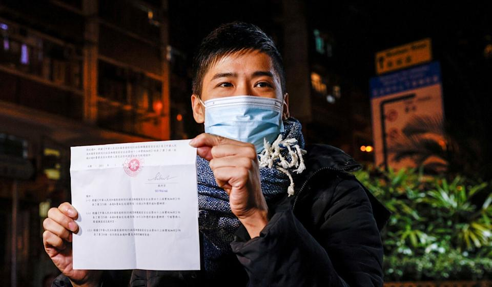 Pro-democracy activist Lester Shum shows his bail document as he leaves Western police station on Thursday night. Photo: Reuters