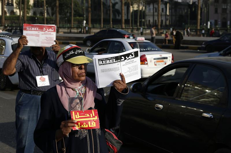 """FILE - In this Sunday, June 23, 2013 file photo, Egyptian activists encourage passersbys to sign a petition by Tamarod, Arabic for """"rebel,"""" a campaign calling for the ouster of Egyptian President Mohammed Morsi, in Cairo, Egypt. A year ago, Egypt's opposition and youth movements demanded the then-ruling military leave power. Now some are counting on its protection as they try to remove Islamist President Mohammed Morsi with a wave of protests. They're hoping the generals, who have signaled discontent with the president, will pressure him out without outright taking over. But Morsi's Islamist backers are already angrily denouncing what they call a potential coup against an elected leader. (AP Photo/Hassan Ammar, File)"""