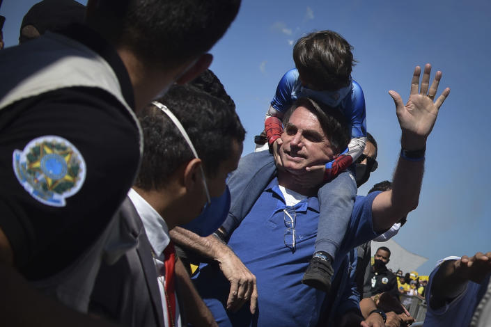 Brazil's President Jair Bolsonaro carries a boy on his back as he greets supporters gathered outside the presidential palace in Brasilia, Brazil, Sunday, May 31, 2020. (AP Photo/Andre Borges)