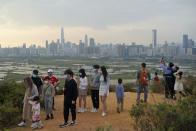 """In this Saturday, Feb. 13, 2021, photo, people visit the border of Hong Kong, with the skyline of China's Shenzhen in the background, in Hong Kong. Hong Kong's Chief Executive Carrie Lam announced a major development plan for Hong Kong's border area with mainland China in the last annual policy address of her current term. The """"Northern Metropolis"""" aims to provide hundreds of thousands more homes and jobs, as well as creating new links across the border. (AP Photo/Kin Cheung)"""