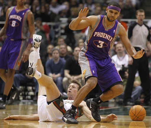 Milwaukee Bucks' Mike Dunleavy, left, falls to the floor after colliding with Phoenix Suns' Jared Dudley (3) during the first half of an NBA basketball game Tuesday, Feb. 7, 2012, in Milwaukee. (AP Photo/Jeffrey Phelps)