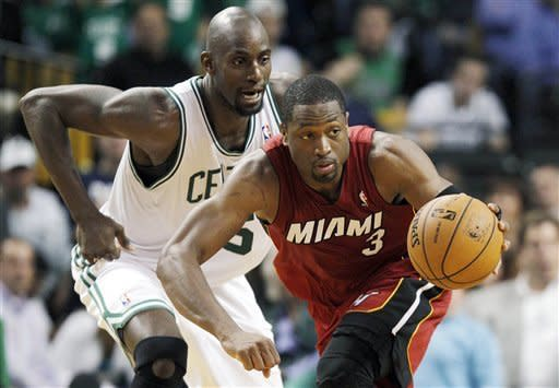 Miami Heat guard Dwyane Wade (3) dribbles away from Boston Celtics forward Kevin Garnett (5) during the fourth quarter in Game 6 of the NBA basketball Eastern Conference finals, Thursday, June 7, 2012, in Boston. (AP Photo/Elise Amendola)
