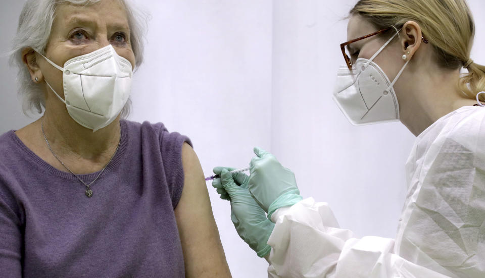 FILE - In this Wednesday, Feb. 17, 2021 file photo, Renate Schulz, left, receives a 'Moderna COVID-19' vaccination by doctor Laura Tosberg, right, at a new coronavirus, COVID-19, vaccination center at the 'Velodrom' (velodrome-stadium) in Berlin, Germany. Germany's health minister Jens Spahn says today the country has now given a first coronavirus vaccine shot to more than half of its population. (AP Photo/Michael Sohn, pool, file)