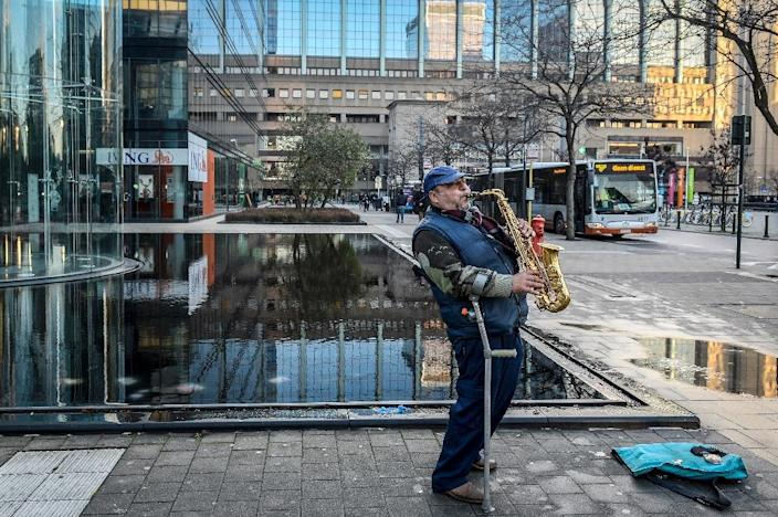 A man plays the saxophone outside office buildings in Brussels as the Belgian capital remains on the highest possible alert level on November 23, 2015 (AFP Photo/Dirk Waem)