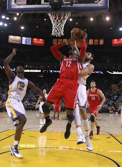 OAKLAND, CA - JANUARY 21: Dwight Howard #12 of the Houston Rockets has a shot blocked by Andrew Bogut #12 of the Golden State Warriors at ORACLE Arena on January 21, 2015 in Oakland, California. NOTE TO USER: User expressly acknowledges and agrees that, by downloading and or using this photograph, User is consenting to the terms and conditions of the Getty Images License Agreement. (Photo by Ezra Shaw/Getty Images)