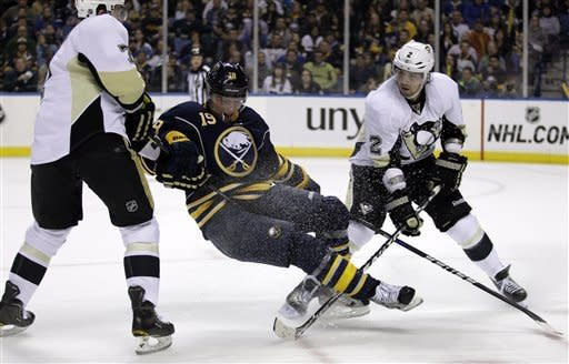 Buffalo Sabres' Cody Hodgson (19) collides with Pittsburgh Penguins' Paul Martin (7) and Matt Niskanen (2) during the first period of an NHL hockey game in Buffalo, N.Y., Friday, March 30, 2012. (AP Photo/David Duprey)
