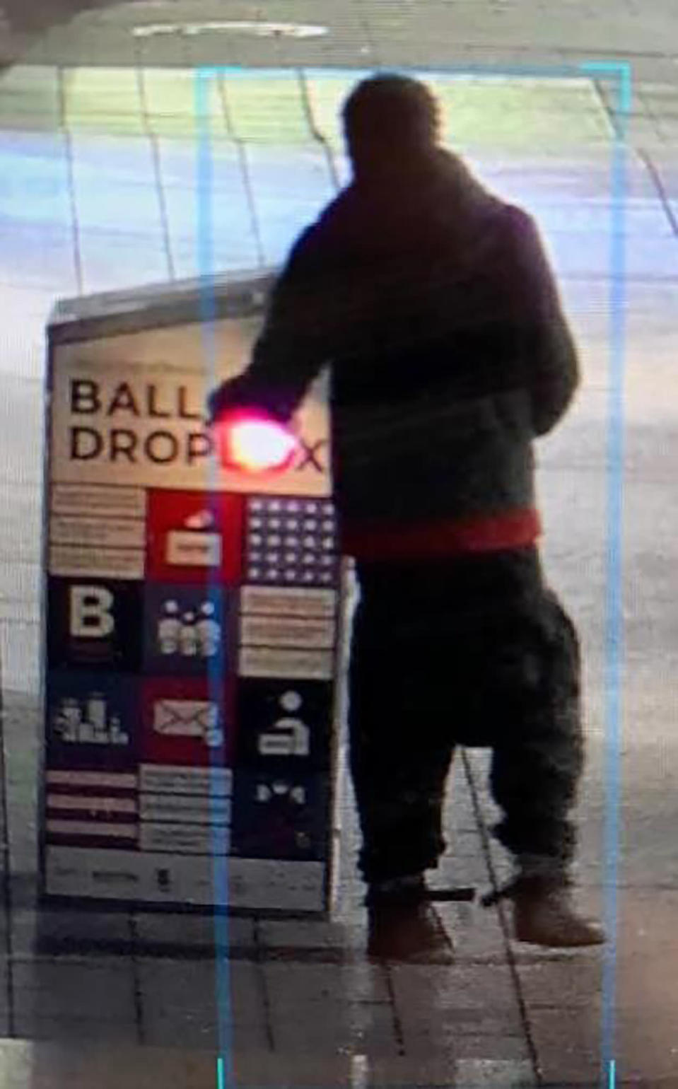 "This surveillance image provided by the Boston Police Department shows a man approaching a ballot drop box outside the Boston Public Library, early Sunday, Oct. 25, 2020, in downtown Boston. Massachusetts election officials say a fire was set at the ballot drop box holding more than 120 ballots in what appears to have been a ""deliberate attack."" Boston Police say that an arson investigation is underway and the person shown in this surveillance image is a person of interest. (Courtesy of Boston Police Department via AP)"