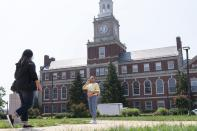 FILE - In this July 6, 2021, file photo with the Founders Library in the background, people walk along the Howard University campus in Washington. With the surprise twin hiring of two of the country's most prominent writers on race, Howard University is positioning itself as one of the primary centers of Black academic thought just as America struggles through a painful crossroads over historic racial injustice. (AP Photo/Jacquelyn Martin, File)