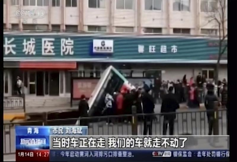 The truck plunged into a sinkhole in the centre of the a street in Xining, Qinghai province, China. Source: CCTV via AP