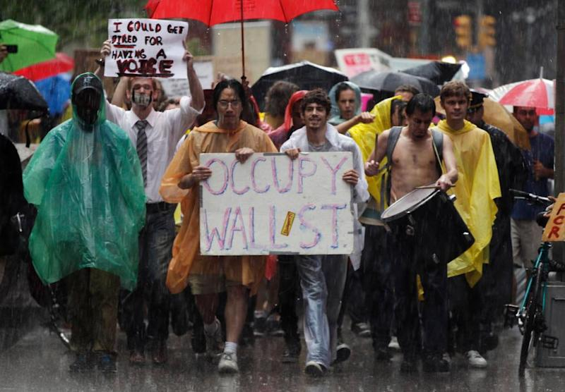 Demonstrators from the Occupy Wall Street campaign march in the rain through the streets of the financial district of New York on 29 September 2011.
