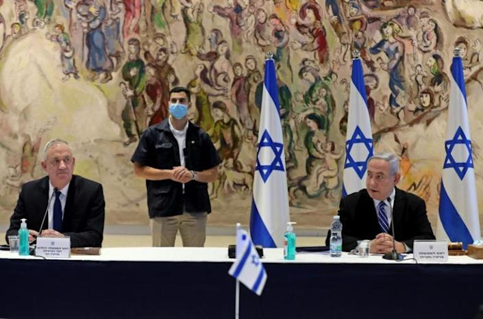 Israeli Prime Minister Benjamin Netanyahu (R) and Alternate Prime Minister and Defence Minister Benny Gantz (L) attend a cabinet meeting of the new government (AFP Photo/ABIR SULTAN)