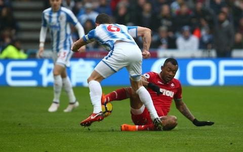 """Carlos Carvalhal needed all of his fire-fighting skills to get Swansea out of Huddersfield with a point. His team were a man down for almost 80 minutes against their relegation rivals, failed to manage a single shot on target and had less than 20 per cent of the possession. In the circumstances, a draw must have felt like a victory. Carvalhal would never admit it publicly, but there must have been a degree of satisfaction in thwarting Huddersfield, who beat his Sheffield Wednesday side on penalties en route to promotion via last season's Championship play-offs. Since moving to south Wales in December, his new team have lost just two of 16 games in all competitions. Survival, which looked highly unlikely at Christmas, is getting closer by the week. They would not have got their draw, though, but for a brilliant save by Lukasz Fabianski with just under half-an-hour to go. The Polish goalkeeper thrust up an arm to get a faint touch after Steve Mounie had hit a thunderous dipping volley. Fabianski's intervention was enough to turn the ball on to the bar. There was an even later escape for the visitors, as Tom Ince headed the excellent Florent Hadergjonaj's cross against the post. Huddersfield were left to rue a failure to score from any of their 28 efforts on goal. Swansea showed no ambition after the early sending off of Jordan Ayew; as far as they were concerned, it was all about putting out """"the fire in the forest"""", as Carvalhal described their fight for survival on Thursday. It was not attractive to watch, but his players got the job done. Andre Ayew was sent off after this tackle on Jonathan Hogg in the 11th minute Credit: Getty Images Ayew, Swansea's 10-goal leading scorer, was sent off in the 10th minute for a reckless challenge on Huddersfield captain Jonathan Hogg. Ayew could have little complaint about the decision; he may have gone into the challenge without any malice, but he went studs first into the midfielder's leg. If Carvalhal had gone into the game wit"""