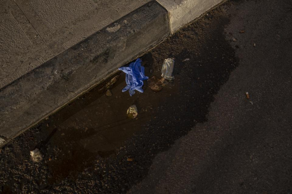 FILE - This April 3, 2020 file photo, shows used medical gloves thrown on a street in Cairo, Egypt. Coronavirus infections are surging in the country of 100 million, threatening to overwhelm hospitals. (AP Photo/Nariman El-Mofty, File)