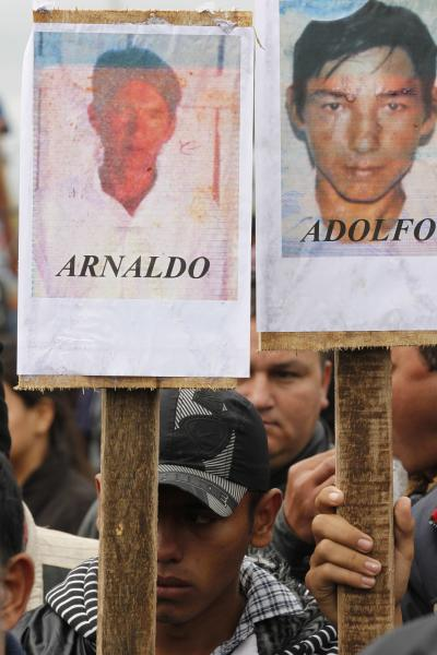 Farmers protest holding pictures of people who died on June 15 in clashes with police as they were evicted from a reserve, on the outskirts of Curuguaty, Paraguay, Thursday, June 21, 2012. The lower house of Paraguay's congress has voted to begin impeachment proceedings against Paraguay's President Fernando Lugo for his role in the violent eviction. Lugo has been heavily criticized over the land eviction last week that killed 17 people in gunbattles between police and landless farmers in a forest reserve. (AP Photo/Jorge Saenz)
