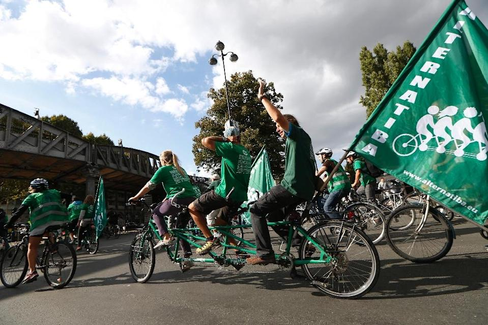 "Activists of the ecologist organisation ""Altenatiba"", ride a three-person tandem bicycle in Paris on September 26, 2015, during a gathering ahead of the World Climate Summit, called the COP21, which starts on November 30 in Paris (AFP Photo/Thomas Samson)"